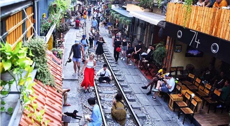 Đường tàu được chọn làm nơi chụp ảnh, khi không có tàu chạy qua, nhiều người thoải mái ngồi giữa đường ray để tạo dáng. (Ảnh qua vnexpress)