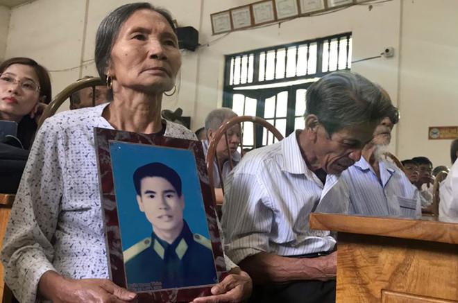 Ông Chinh ngẹn ngào ngồi cùng em dâu, ôm di ảnh em trai ruột khi nghe cháu kể về quá trình đi tìm công lý cho bố.