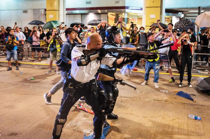 """Cảnh sát đầu trọc Lưu Trạch Cơ thời gian gần đây tuyên bố sẽ về Trung Quốc Đại lục sinh sống. Người Hồng Kông vỗ tay """"Mau đi đi, đừng trở về nữa. Vị cảnh sát này từng bị chỉ trích khi giương súng trường chĩa thẳng vào người biểu tình. (Ảnh: )"""