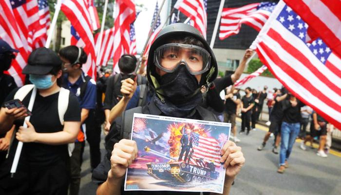 Một người biểu tình Hong Kong cầm bức ảnh Tổng thống Trump trong cuộc tuần hành trước lãnh sự quán Mỹ hôm 8/9.