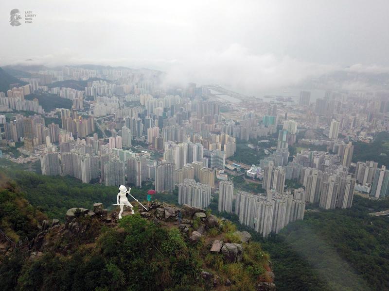 """Tượng nữ thần cầm cây dù và lá cờ với dòng chữ """"Khôi phục Hồng Kông, Cách mạng thời đại"""""""