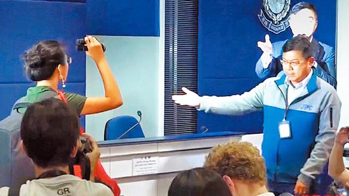 Nữ phóng viên Hồng Kông dùng đèn pin rọi vào quan chức cảnh sát cấp cao mô phỏng tình hình những người phóng viên bị rọi đèn.