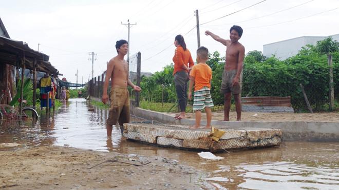 Nước ngập sâu, người dân phải kết phao để trẻ em đi lại.