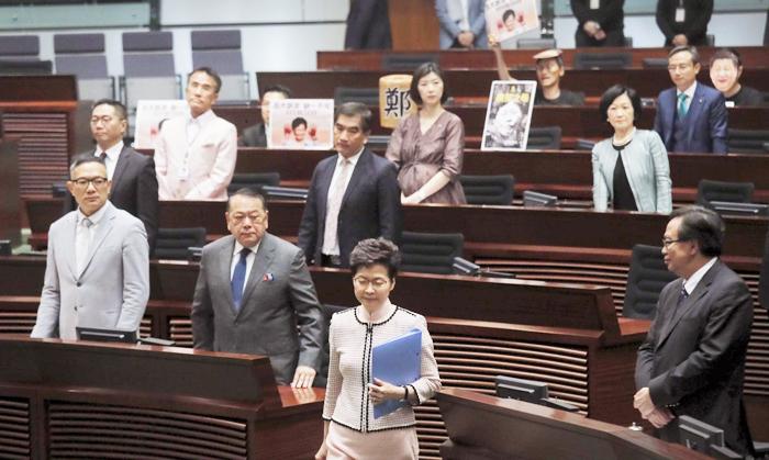 """Các nghị viên đối lập ở Hồng Kông đưa hình Đặc Khu Trưởng Carrie Lam với đôi tay """"vấy máu"""" trong nghị trường."""