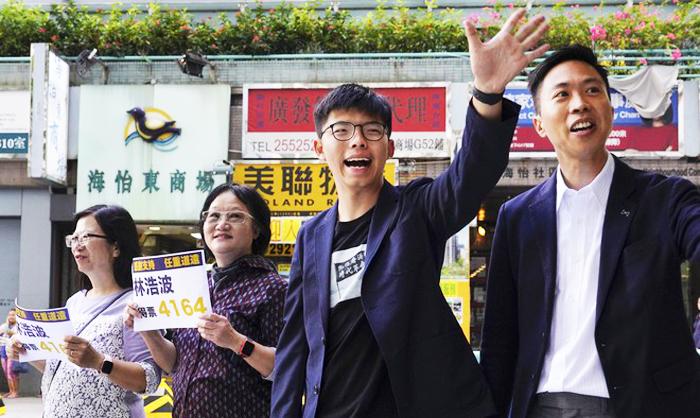 Ứng viên thắng cử của phe dân chủ Kelvin Lam và Joshua Wong vẫy tay, cám ơn sự ủng hộ của cử tri.
