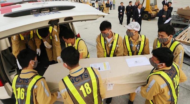 Quan tài nạn nhân được đưa vào xe cứu thương để chở về quê.