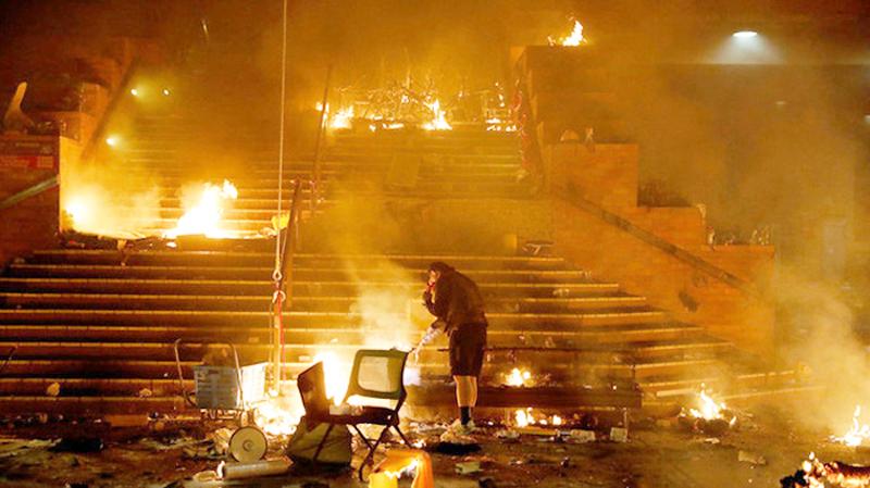 Một người biểu tình đốt lửa ở lối vào trường PolyU nhằm cản trở cảnh sát, rạng sáng 18/11.
