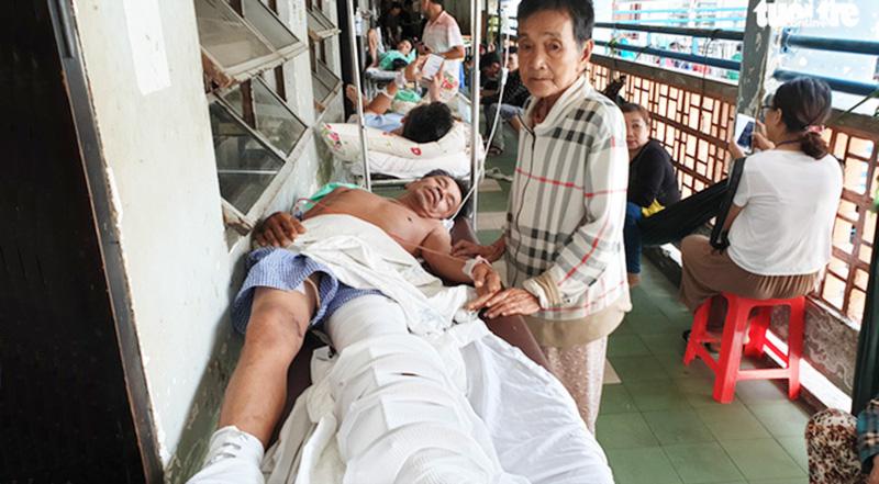 Bà Khinh chăm sóc con trai bị tai nạn gãy chân trong bệnh viện.