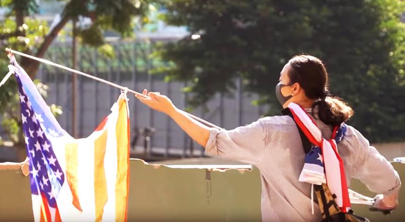 Đầu bếp David Yang vẫy cờ Mỹ đi tìm những người biểu tình còn ẩn nấp trong PolyU nhưng không chịu ra ăn.