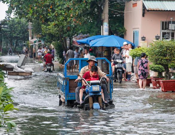 Đường Phạm Hùng, huyện Bình Chánh ngập nặng, gây khó khăn cho người dân qua lại. (Ảnh qua tuoitre)