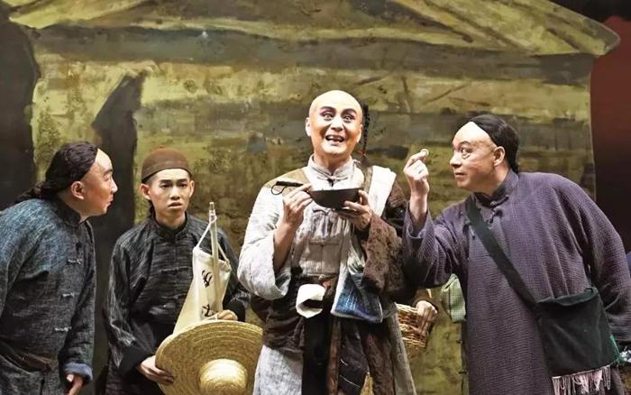 Vũ Huấn mặc trang phục kỳ dị như một anh hề mua vui cho khách qua đường, âu cũng là mong có thêm tiền thưởng tặng.