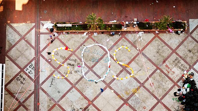 Người biểu tình ở PolyU xếp biểu tượng cứu viện SOS trên mặt đất để truyền thông tin xin trợ giúp ra thế giới bên ngoài.