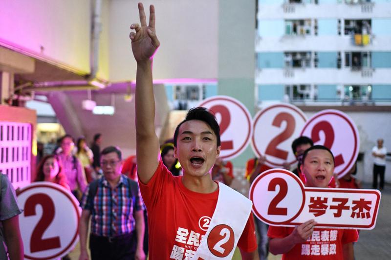 Ứng cử viên ủng hộ dân chủ Jimmy Sham (giữa) đi vận động vào ngày bỏ phiếu.