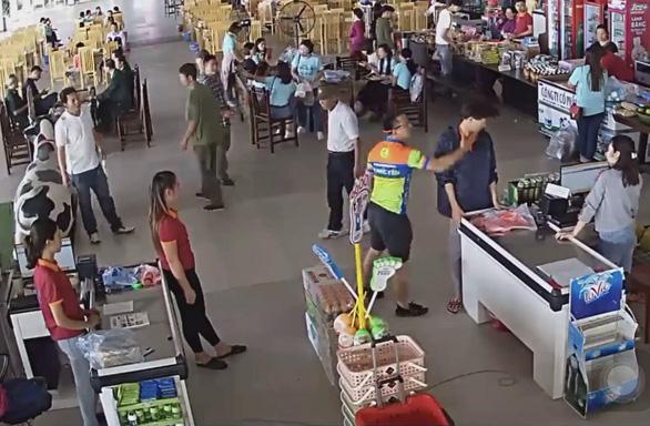 Không chỉ ném xích xích về phía nhân viên nữ, người đàn ông này còn đi tới, tát mạnh vào mặt một nam nhân viên khác. (Ảnh cắt từ clip)