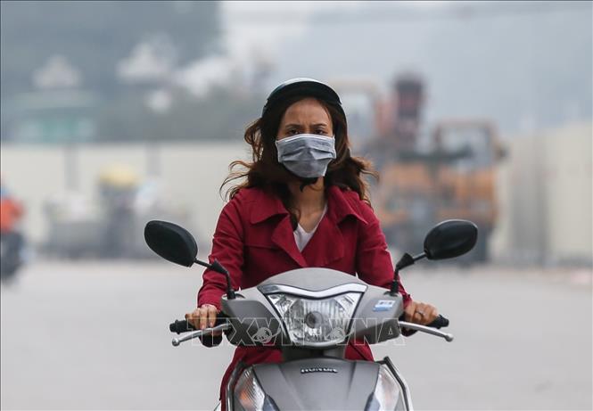 Đeo khẩu trang khi ra đường dù là buổi sáng sớm đã là thói quen của người dân Thủ đô để bảo vệ bản thân trước tình trạng ô nhiễm không khí đang ngày một nghiêm trọng. (Ảnh qua ttxvn)