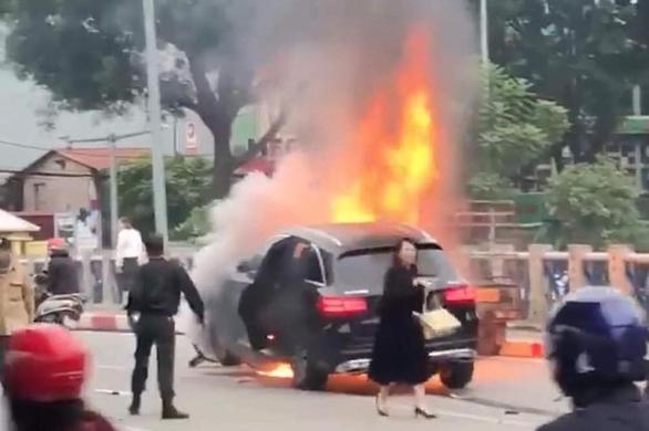Nữ tài xế hoảng loạn chạy ra khỏi chiếc xe bốc cháy sau khi gây tai nạn.
