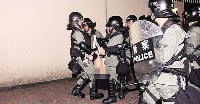Người biểu tình nữ bị đám đông cảnh sát khống chế dẫn đến lộ thân thể.