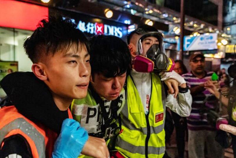 Một phóng viên đã không được khỏe khi bị cảnh sát xịt nước tiêu trúng, nhân viên cứu hộ giúp đỡ anh ta rời đi.