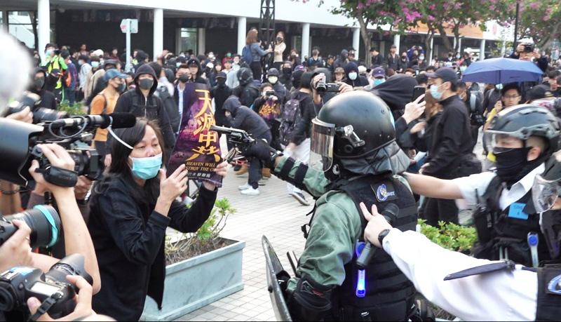 """Ngày 22/12, người Hồng Kông diễu hành tại Trung Hoàn để ủng hộ người Duy Ngô Nhĩ, một người biểu tình giơ lên biểu ngữ """"Trời diệt Trung Cộng"""" đã bị cảnh sát rút súng lục ra đe dọa."""