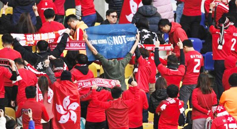 """Người hâm mộ bóng đá Hồng Kông đã giương cao biểu ngữ """"Khôi phục Hồng Kông"""" và hát bài hát quen thuộc """"Nguyện vinh quang quy Hương Cảng""""."""
