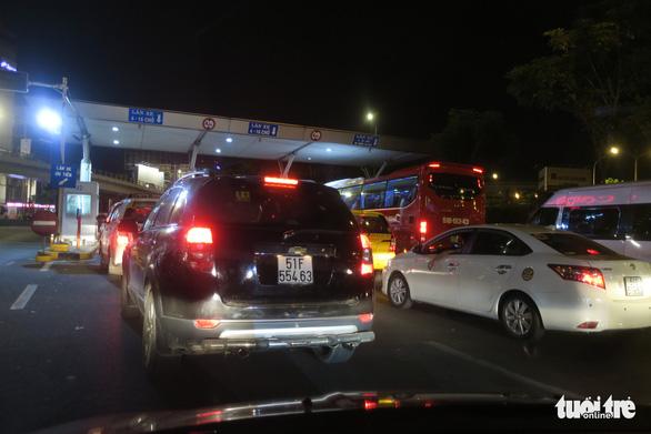 Hệ thống thu phí bị trục trặc làm các xe bị ùn ứ khi ra khỏi sân bay. Nhân viên phải hướng dẫn các xe di chuyển sang làn ưu tiên (bên trái) rồi bán và soát vé thủ công. (Ảnh qua tuoitre)