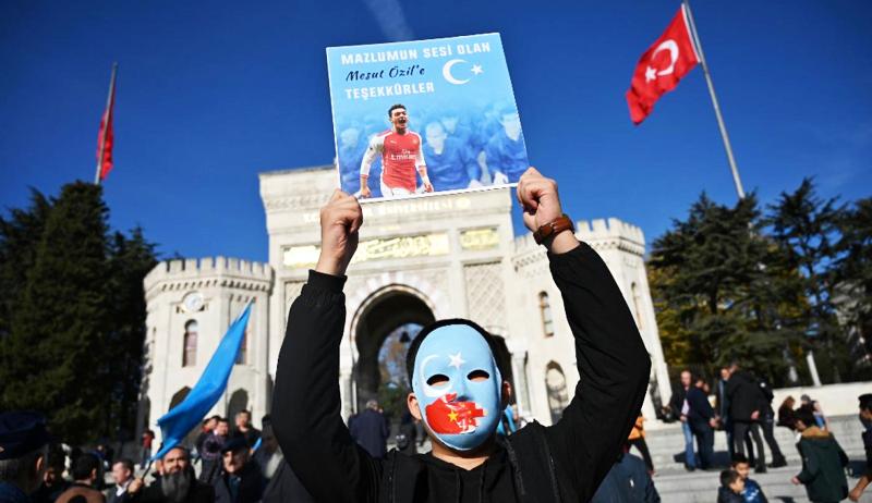 Người Duy Ngô Nhĩ ở Istanbul giữ giương cao hình ảnh của Mesut Ozil.
