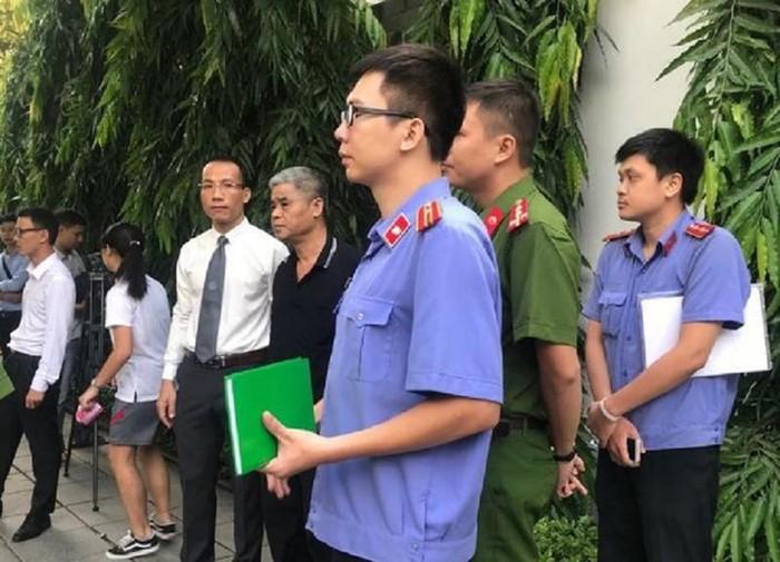 Bị can Doãn Quý Phiến (áo đen) trong một lần thực nghiệm hiện trường vụ án.