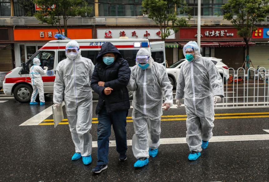 Nhân viên y tế mặc đồ bảo hộ đi cùng một bệnh nhân vào một bệnh viện ở Vũ Hán hôm 26/1/2020.