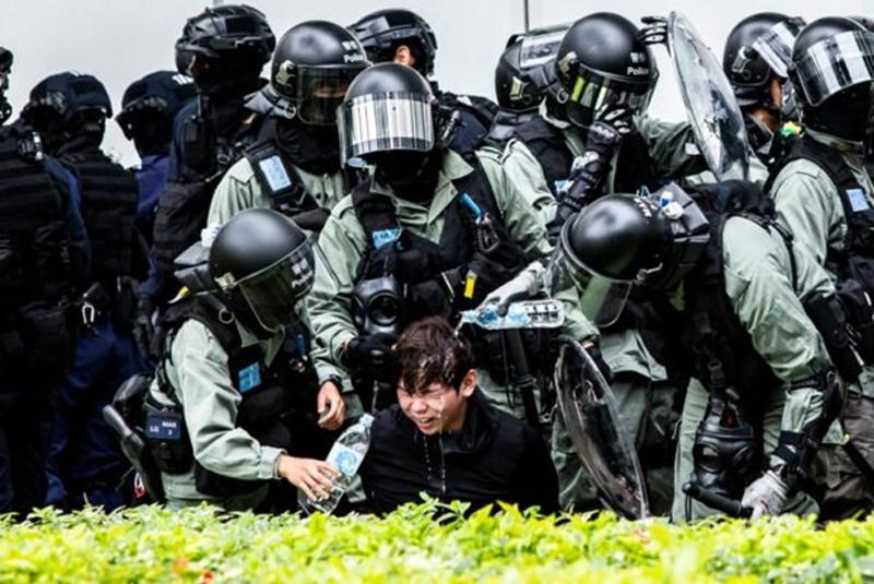 Một cảnh sát mặc thường phục cũng bị cảnh sát chống bạo động điên cuồng xịt hơi cay vào mặt.