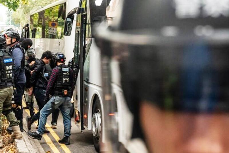Người dân bị bắt bị áp giải lên xe bus mang đi.