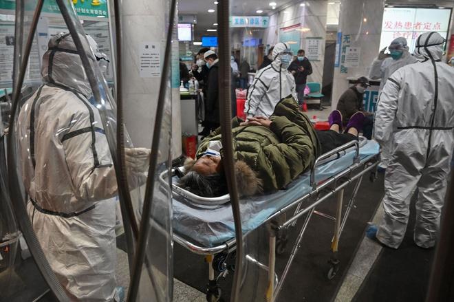 Nhân viên y tế mang đồ bảo hộ đưa một bệnh nhân nhiễm virus corona vào bệnh viện Chữ thập Đỏ thành phố Vũ Hán hôm 25/1. (Ảnh qua Zing)