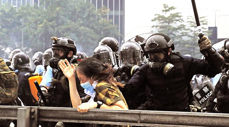 Ngày 12/6, cảnh sát Hồng Kông trong lúc xua đuổi người biểu tình đã vây quanh một người phụ nữ.