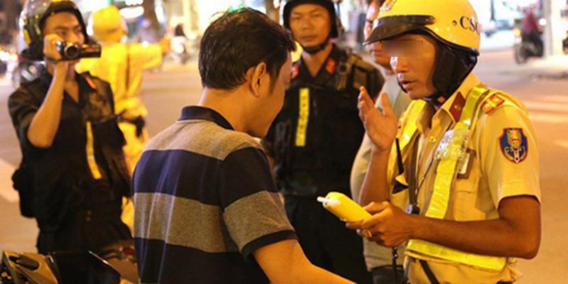 Cảnh sát giao thông kiểm tra nồng độ cồn trong hơi thở tài xế.