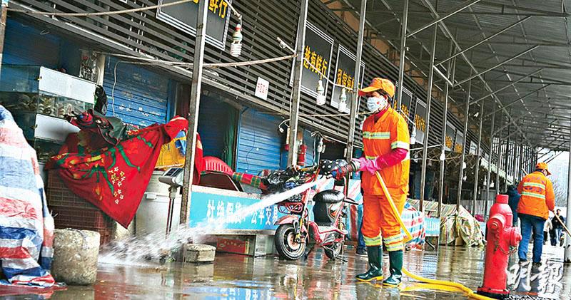 tại chợ hải sản Hoa Nam, các nhân viên mặc quần áo phòng cháy chữa cháy màu trắng đang phun thuốc vào cửa của nhiều cửa hàng và cổng sắt ở hai bên hành lang.