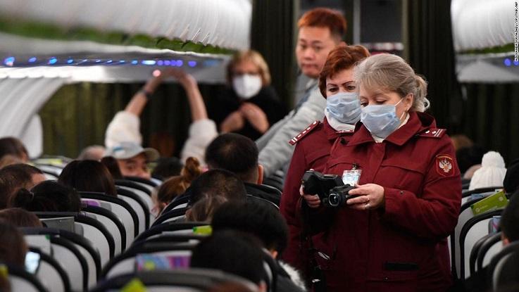 Các nhân viên an ninh đo thân nhiệt của hành khách trên một chuyến bay khởi hành từ Bắc Kinh hạ cánh xuống sân bay Tolmachevo, Novosibirsk, Nga. (Ảnh qua AP)