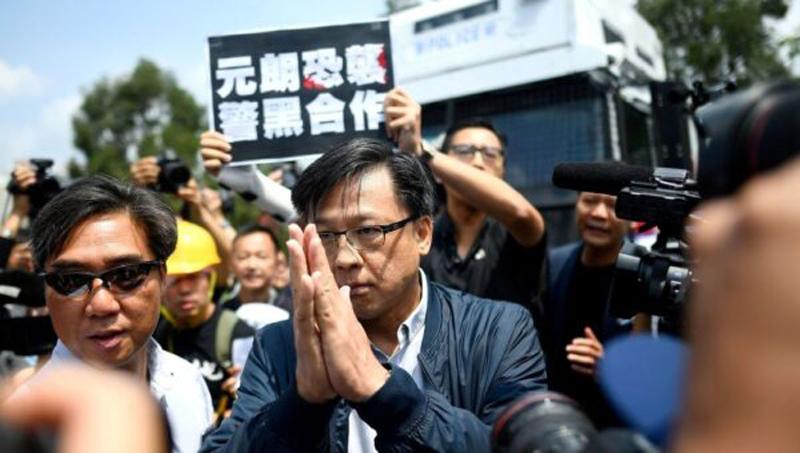 """Trong tấm ảnh Junius Ho bị giới truyền thông bao vây phỏng vấn, có người đàn ông giơ tấm biển khẩu hiệu """"Khủng bố ở Yuen Long, cảnh sát và xã hội đen hợp tác"""" phản đối việc ông Ho thông đồng với băng đảng xã hội đen để tấn công người dân."""