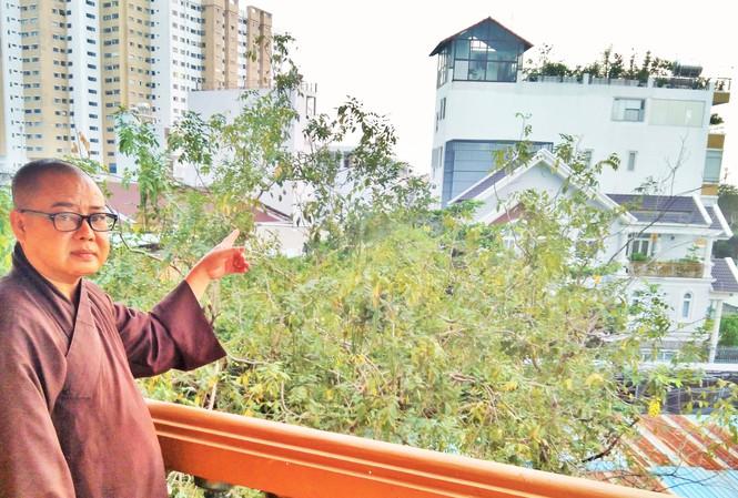 Hòa thượng Thích Từ Trí chỉ một ngôi nhà cao tầng đã xây dựng trên đất chùa cổ Giác Lâm. (Ảnh qua tienphong)