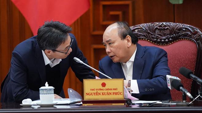 Thủ tướng trao đổi với Phó thủ tướng Vũ Đức Đam bên lề cuộc họp. (Ảnh qua thanhnien)
