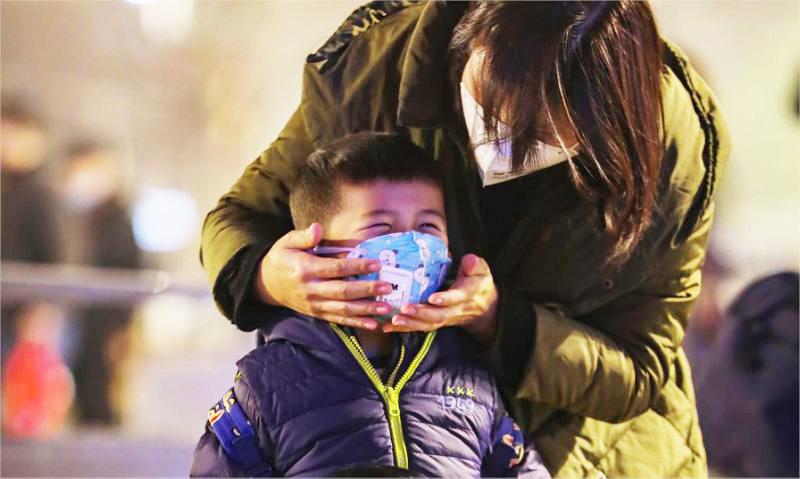 Một bà mẹ kiểm tra khẩu trang của con bên ngoài nhà ga Hán Khẩu ở Vũ Hán.