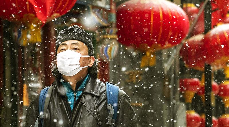 Ngày 5/2, một người đàn ông đeo khẩu trang đi trên đường phố ở Bắc Kinh trong khí trời tuyết lạnh.