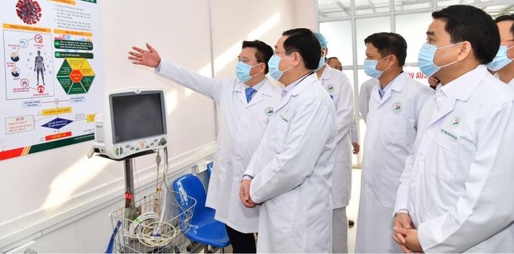Bí thư Thành uỷ Hà Nội Vương Đình Huệ nghe lãnh đạo Bệnh viện đa khoa Đức Giang báo cáo công tác phòng, chống dịch. (Ảnh qua vnexpress)