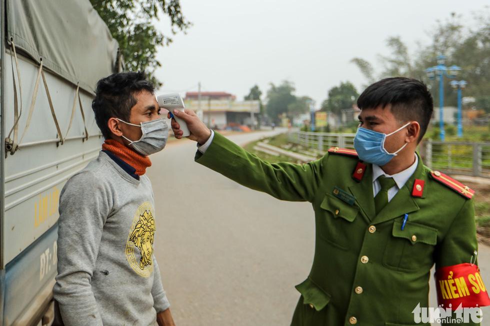 Một người dân được kiểm tra thân nhiệt khi đi qua chốt kiểm dịch. Hiện tại, xã Sơn Lôi đã có 5 người bị nhiễm virus corona. (Ảnh qua tuoitre)