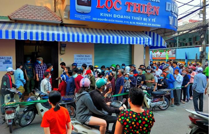 Người dân tại TP.HCM đứng xếp hàng dài đợi mua khẩu trang. (Ảnh qua vietnammoi)