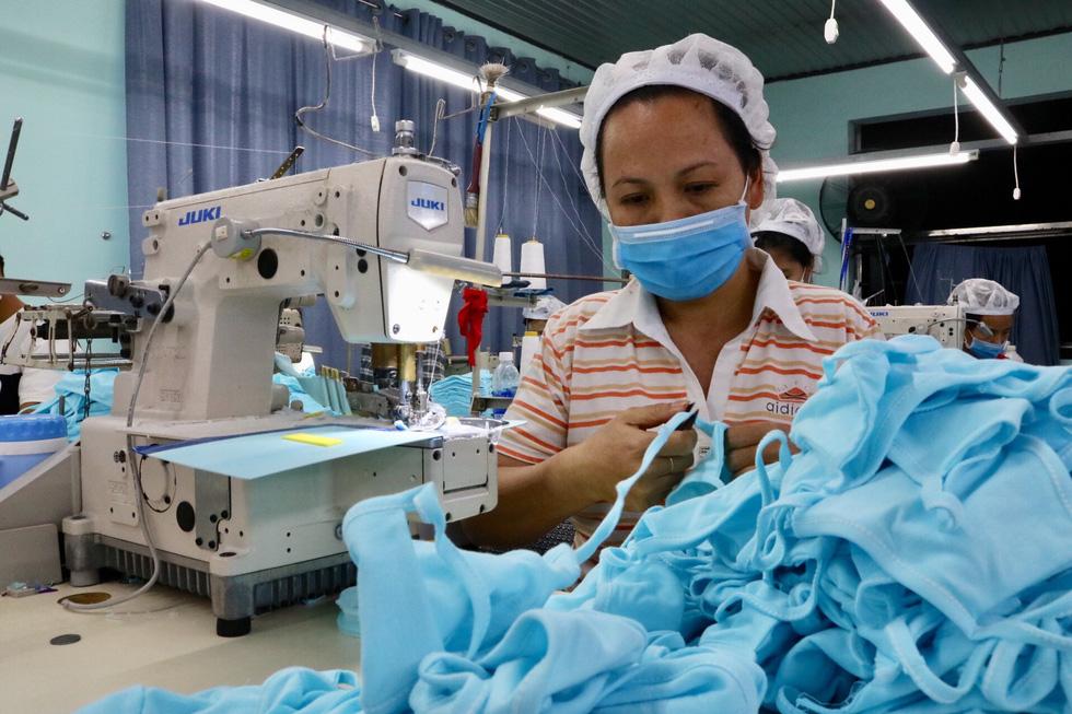 Vải ráp xong sẽ được công nhân đi dây theo viền có sẵn, tạo thành quai đeo. (Ảnh qua tuoitre)