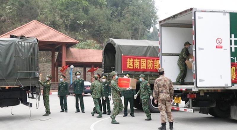 Lực lượng chức năng Việt Nam vận chuyển trang thiết bị thiết bị y tế phòng, chống dịch Covid-19 bàn giao cho phía Trung Quốc. (Ảnh qua nld)