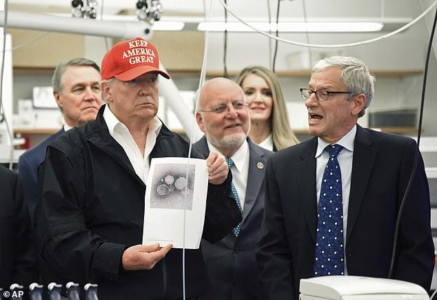 Hình ảnh vị tổng thống Mỹ cầm trên tay bức ảnh chụp virus corona tại trụ sở chính của Trung tâm Kiểm soát và Phòng ngừa Dịch bệnh tại Atlanta.