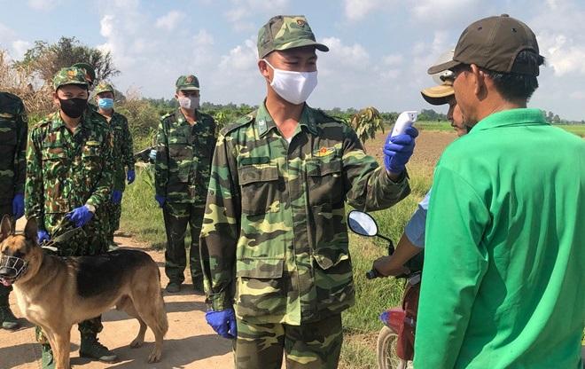 Bộ đội biên phòng An Giang kiểm tra thân nhiệt người dân khu vực biên giới Vĩnh Xương. (Ảnh qua thanhnien)