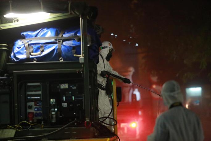 Quân đội tiến hành khử khuẩn tại Bệnh viện Bạch Mai tối 28/3. (Ảnh qua nld)