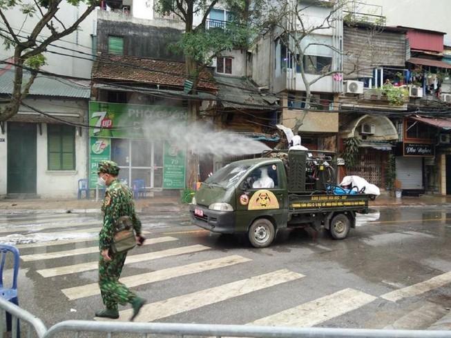 Lực lượng quân đội tiến hành phun thuốc khử trùng tại một số tuyến phố trên địa bàn phường Trúc Bạch. (Ảnh qua Plo)