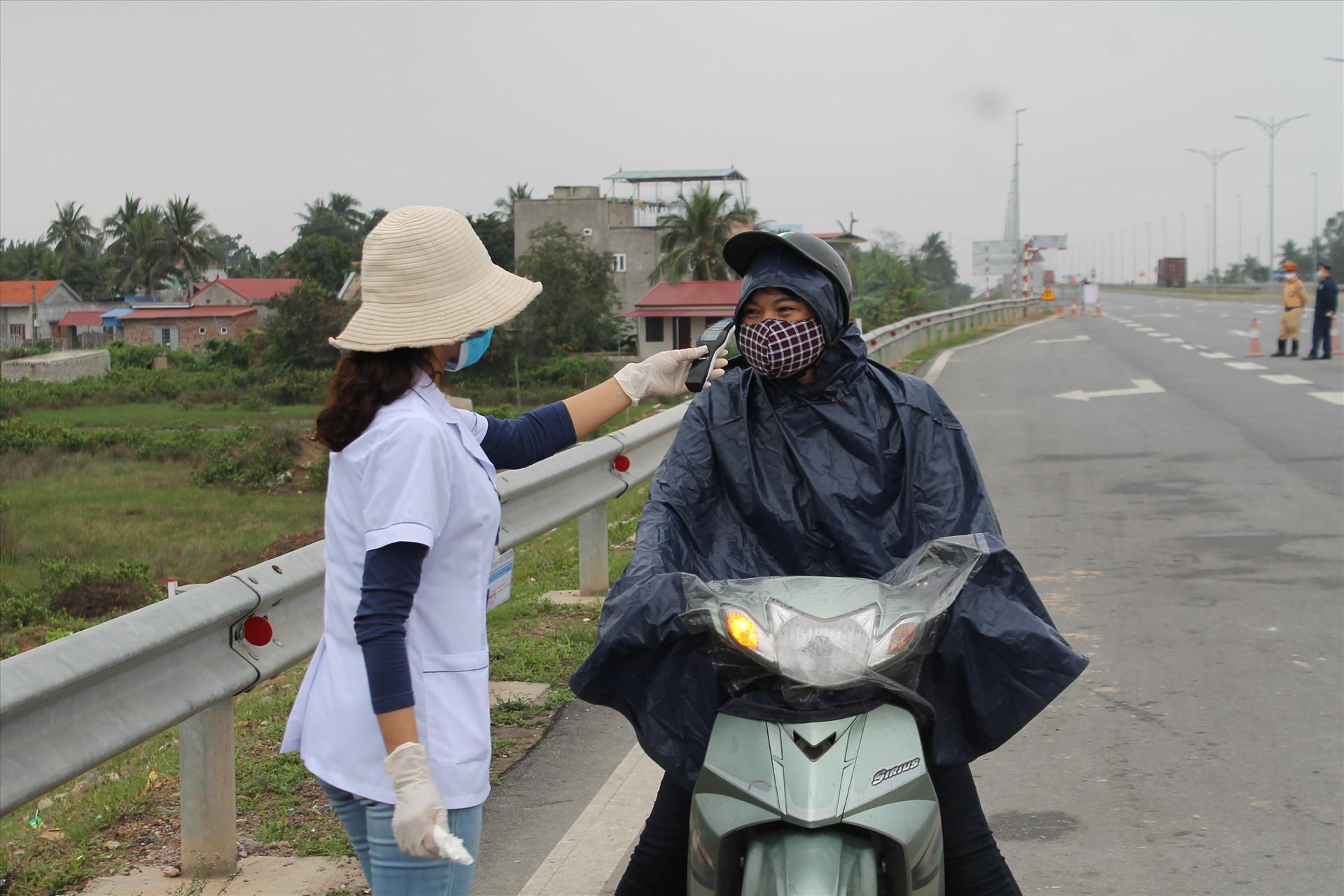 Kiểm tra thân nhiệt tại chốt kiểm dịch y tế huyện Cát Hải. (Ảnh qua laodong)